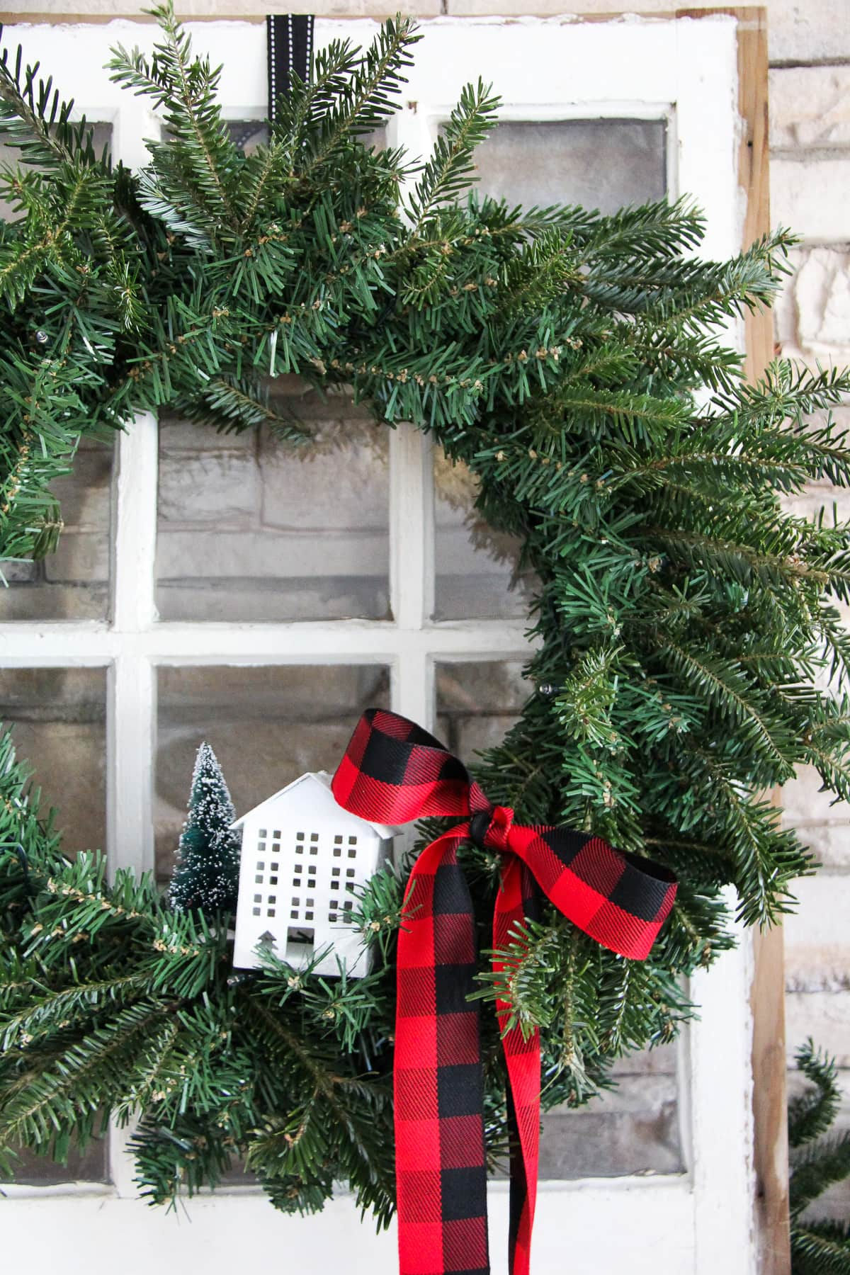 Pretty Evergreen Wreath. Just add fresh evergreen sprigs to a faux evergreen wreath to make it look more authentic.