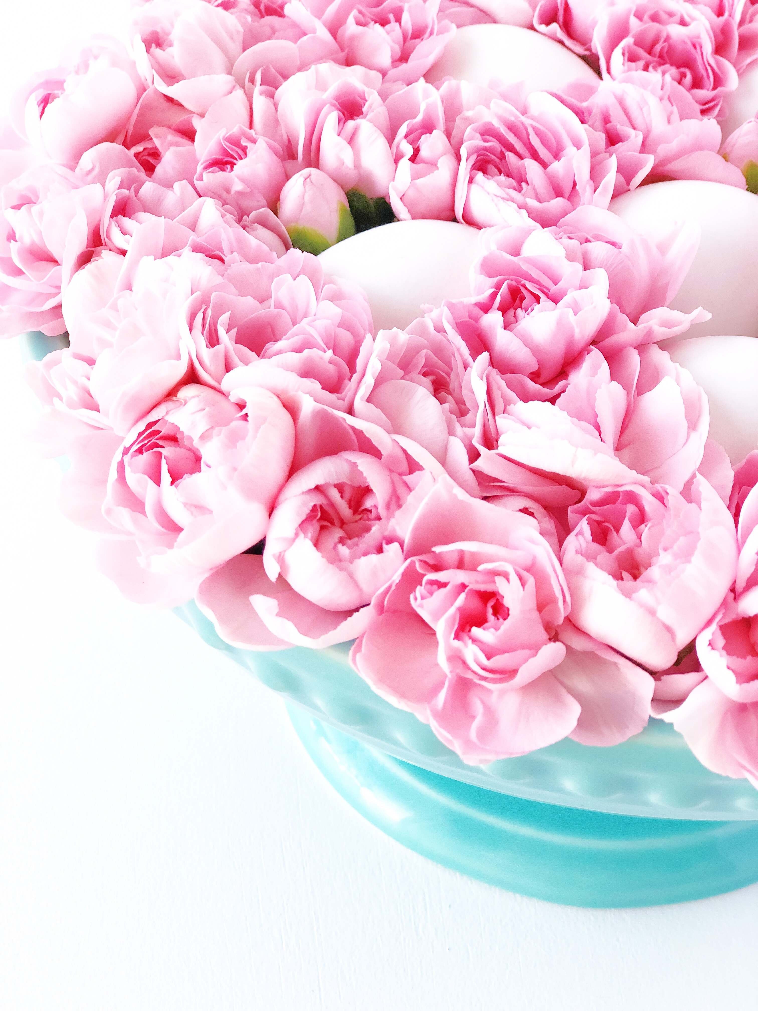 A gorgeous egg and fresh pink carnation centerpiece arrangement.